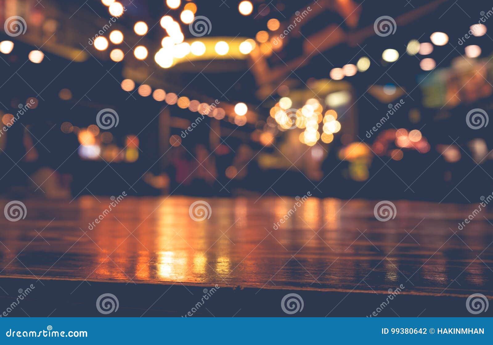 Barra de madeira vazia do tampo da mesa no restaurante do café do borrão no fundo escuro