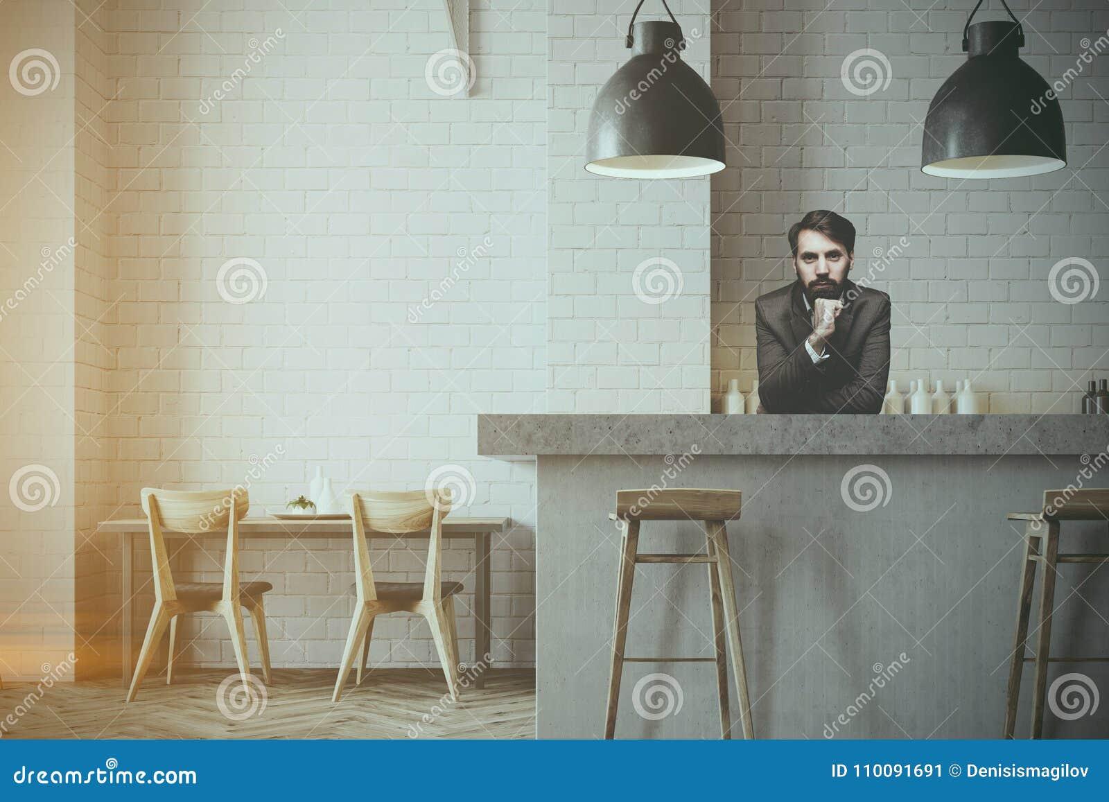 Barra de pared e interior grises del café, camarero