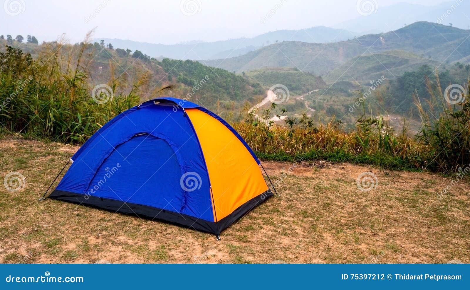 Barraca de acampamento azul e amarela do turista na área de recreação entre o prado na floresta da montanha