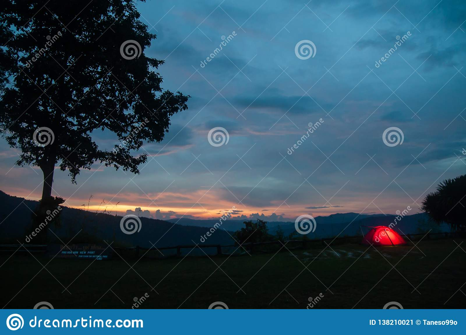 Barraca de acampamento iluminada no crepúsculo sob o céu do por do sol no pico de montanha Beira de Tailandês-Laos Phu Suan Sai N