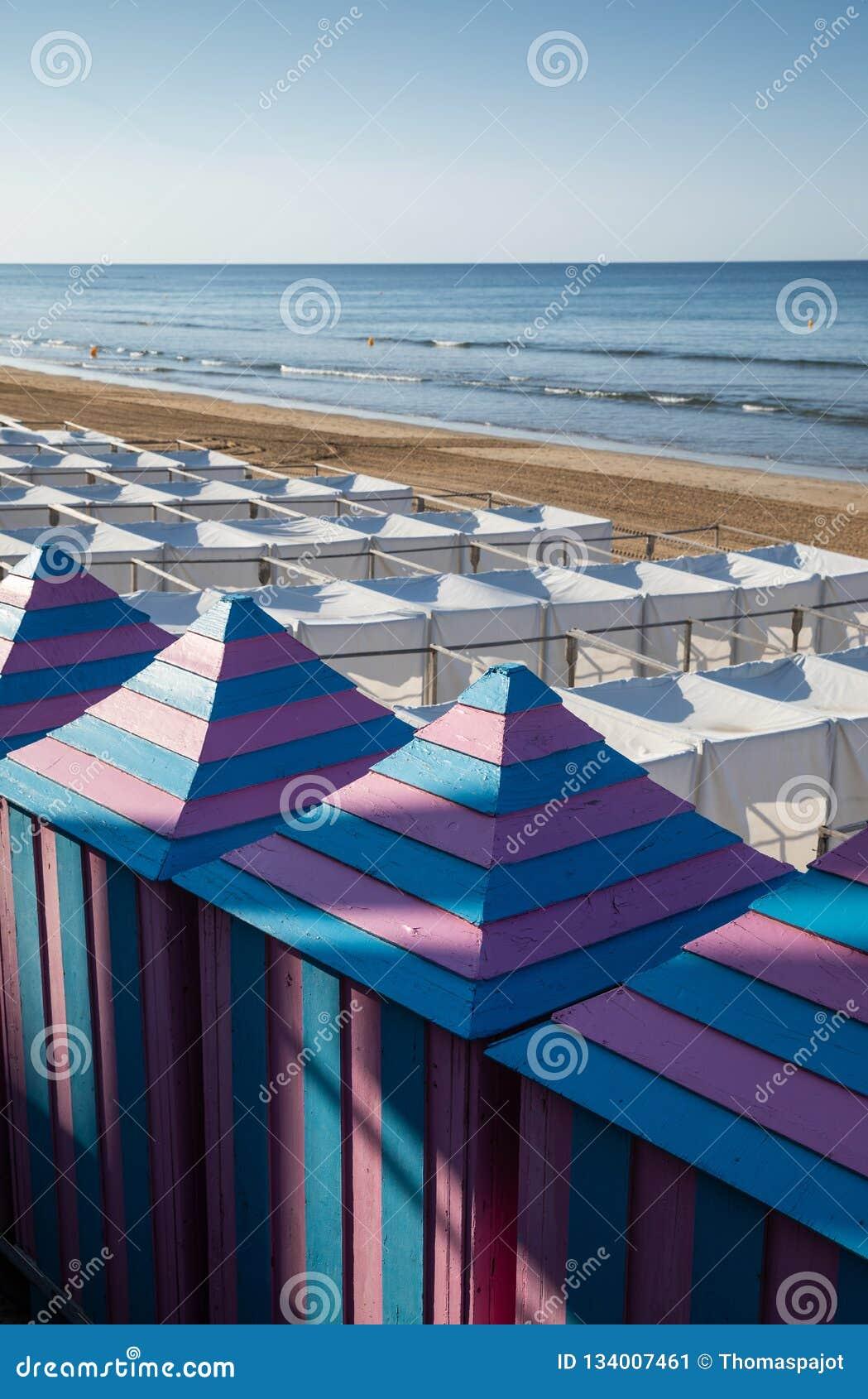 Barracas brancas e cabines cor-de-rosa azuis na praia