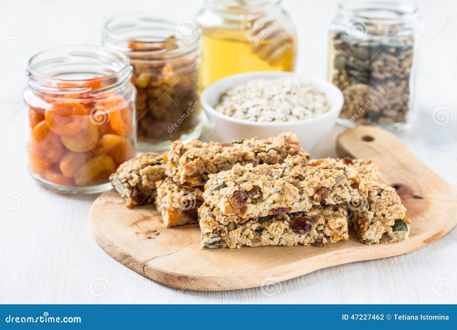 Barras e ingredientes caseiros saudáveis de granola no fundo