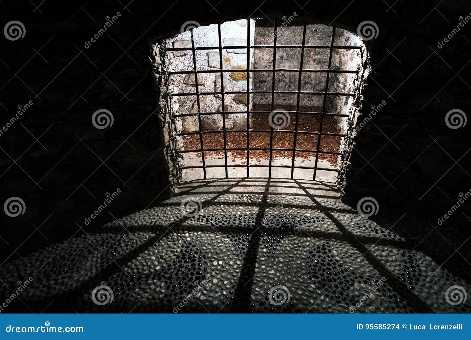 Barras medievais da pilha da prisão escura velha do Dungeon