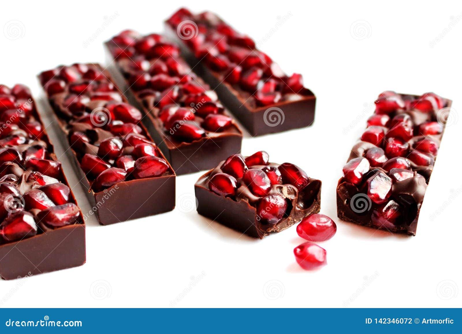 Barre di cioccolato fondente del melograno su fondo bianco