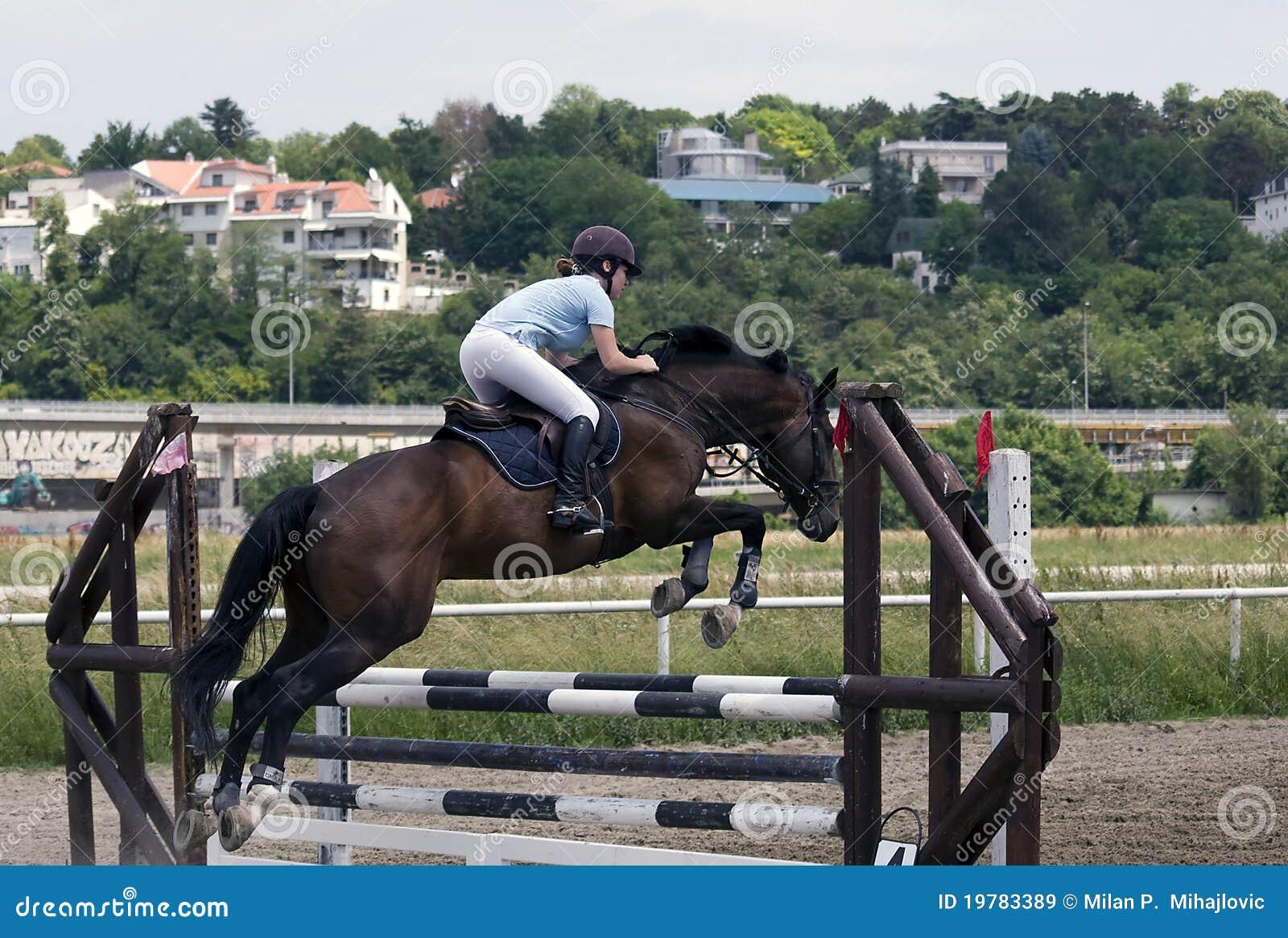 Barriärhästbanhoppning över ryttare