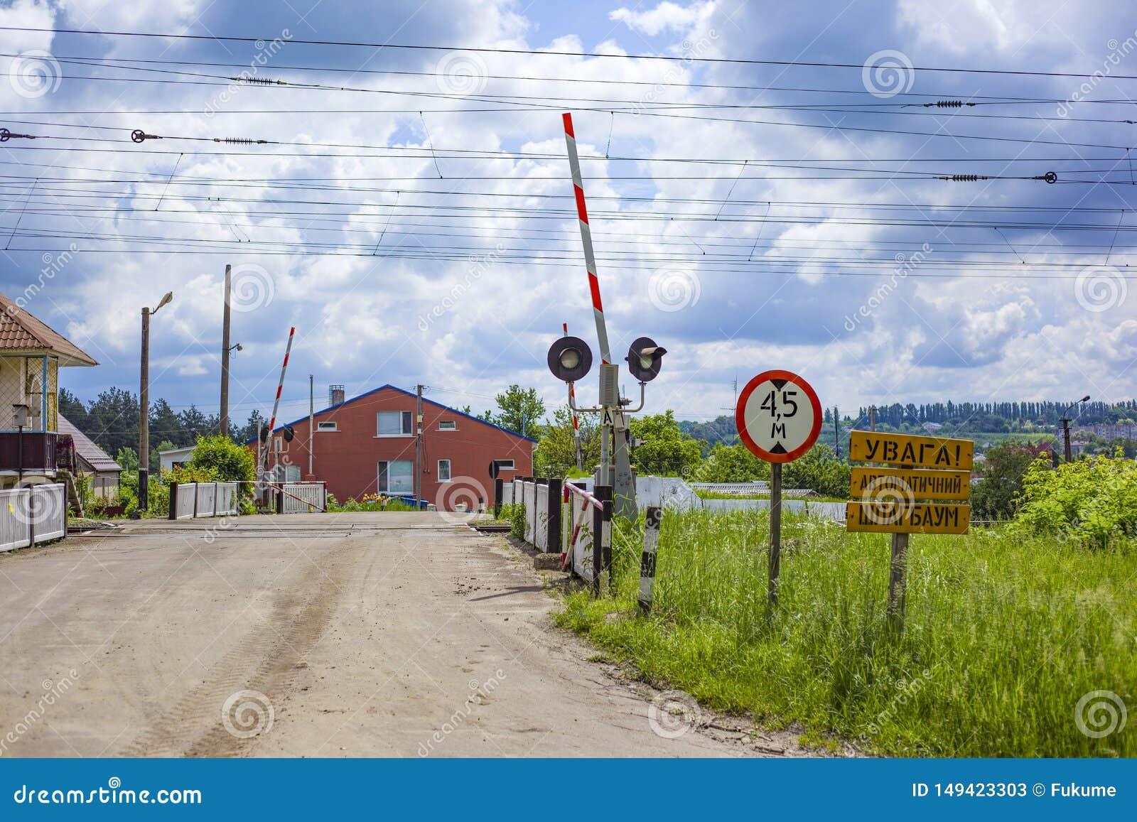 Barrière ferroviaire ouverte avec des panneaux routiers dans un petit village en Ukraine