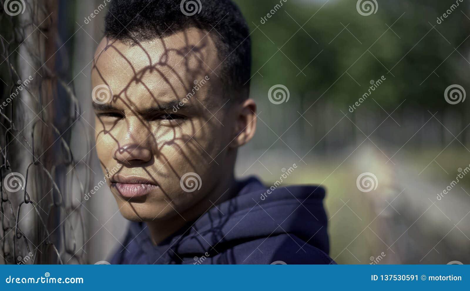 Barrière se tenante prêt en métal de pauvre adolescent afro-américain, concept de difficultés de la vie