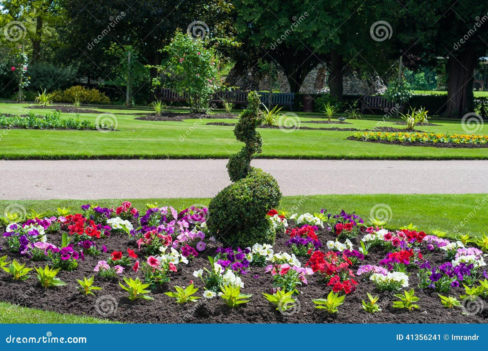 Barriera a spirale verde in mezzo alle piante floreali da for Piante da aiuola
