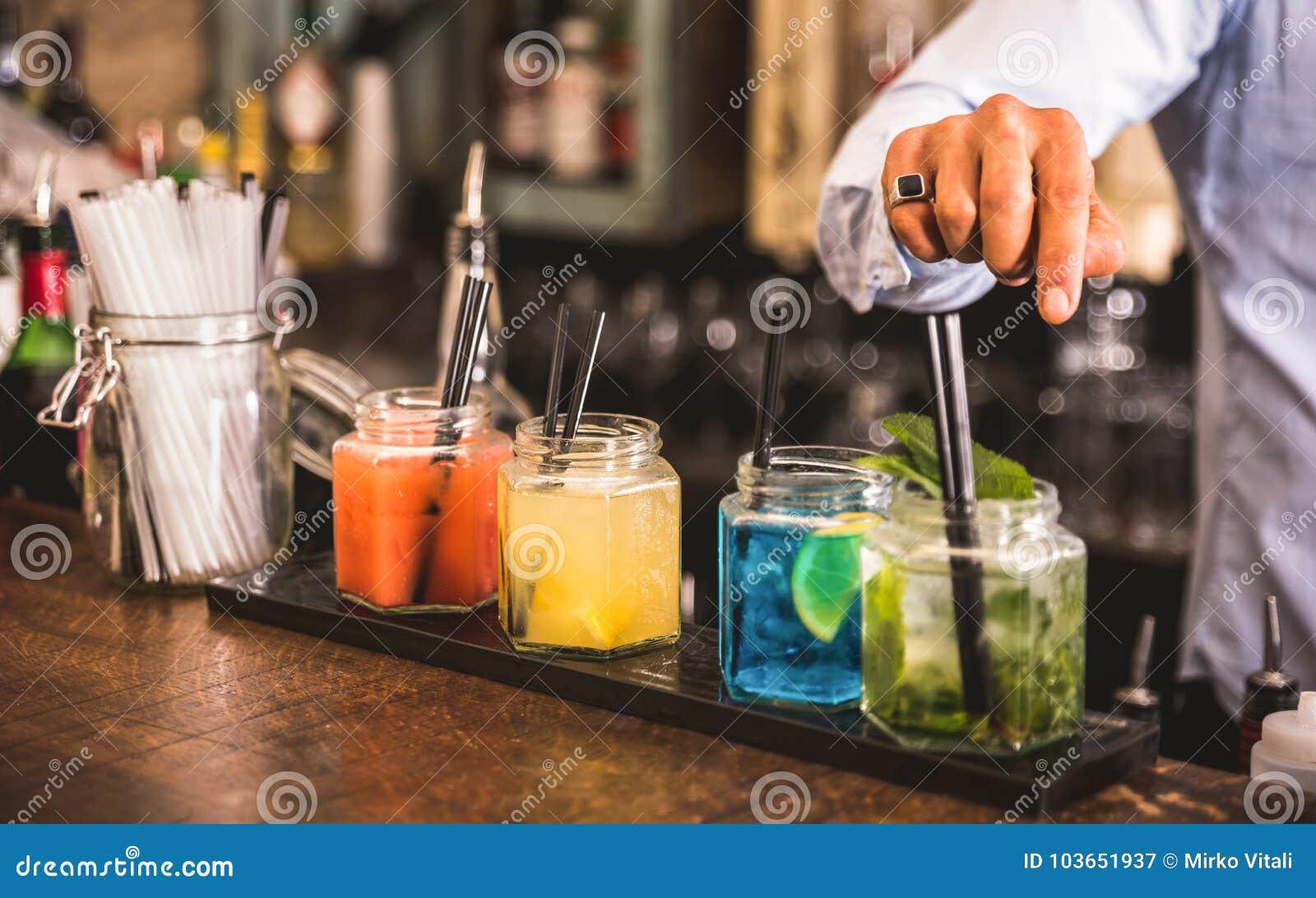Bartender χέρι στα πολύχρωμα ποτά μόδας στο φραγμό κοκτέιλ