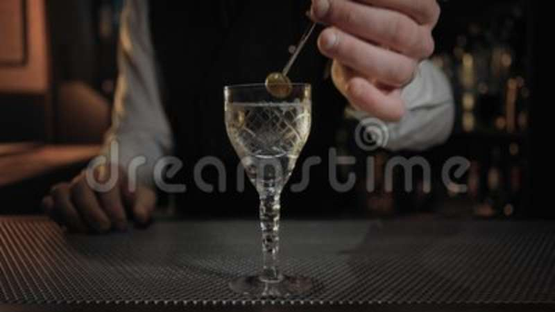bartender adds olive to neat dry martini cocktail stock footage
