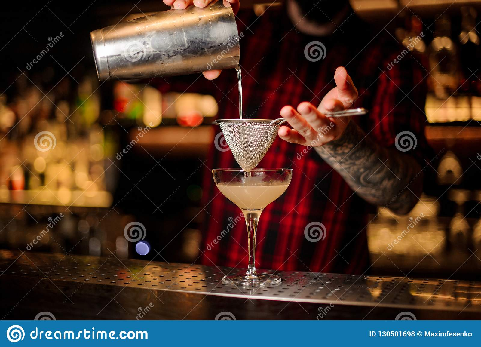 Bartender pourring a Daiquiri cocktail from the shaker through t