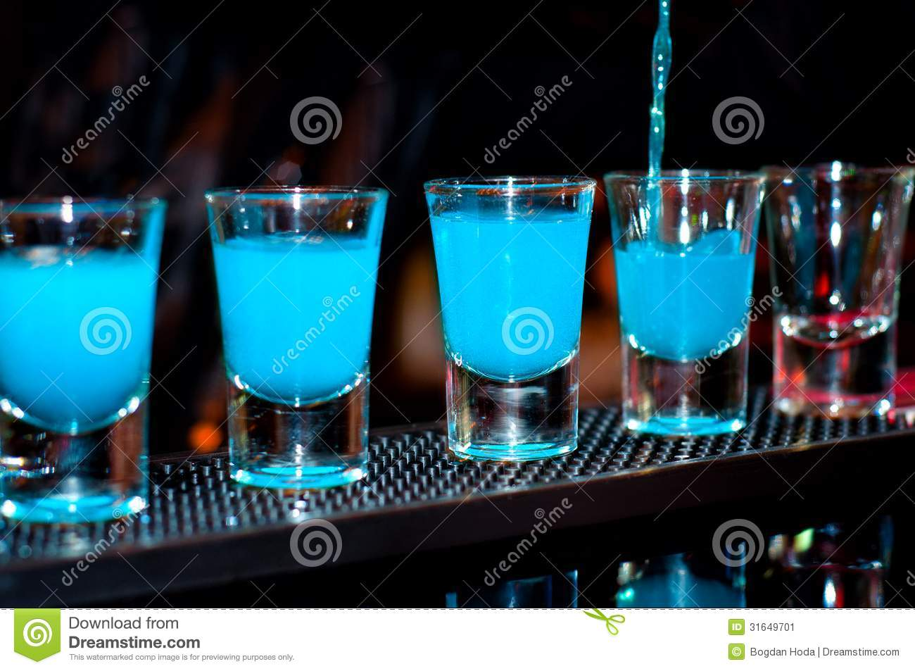 Bartender pours blue alcoholic drink into small glasses on bar