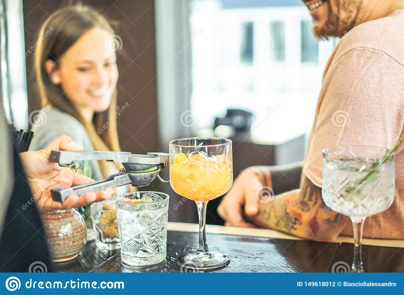 Bartender som f?rbereder coctailar som ut h?ller limefrukt - lyckliga v?nner som v?ntar p? drinkar p? r?knaren i amerikansk st?ng