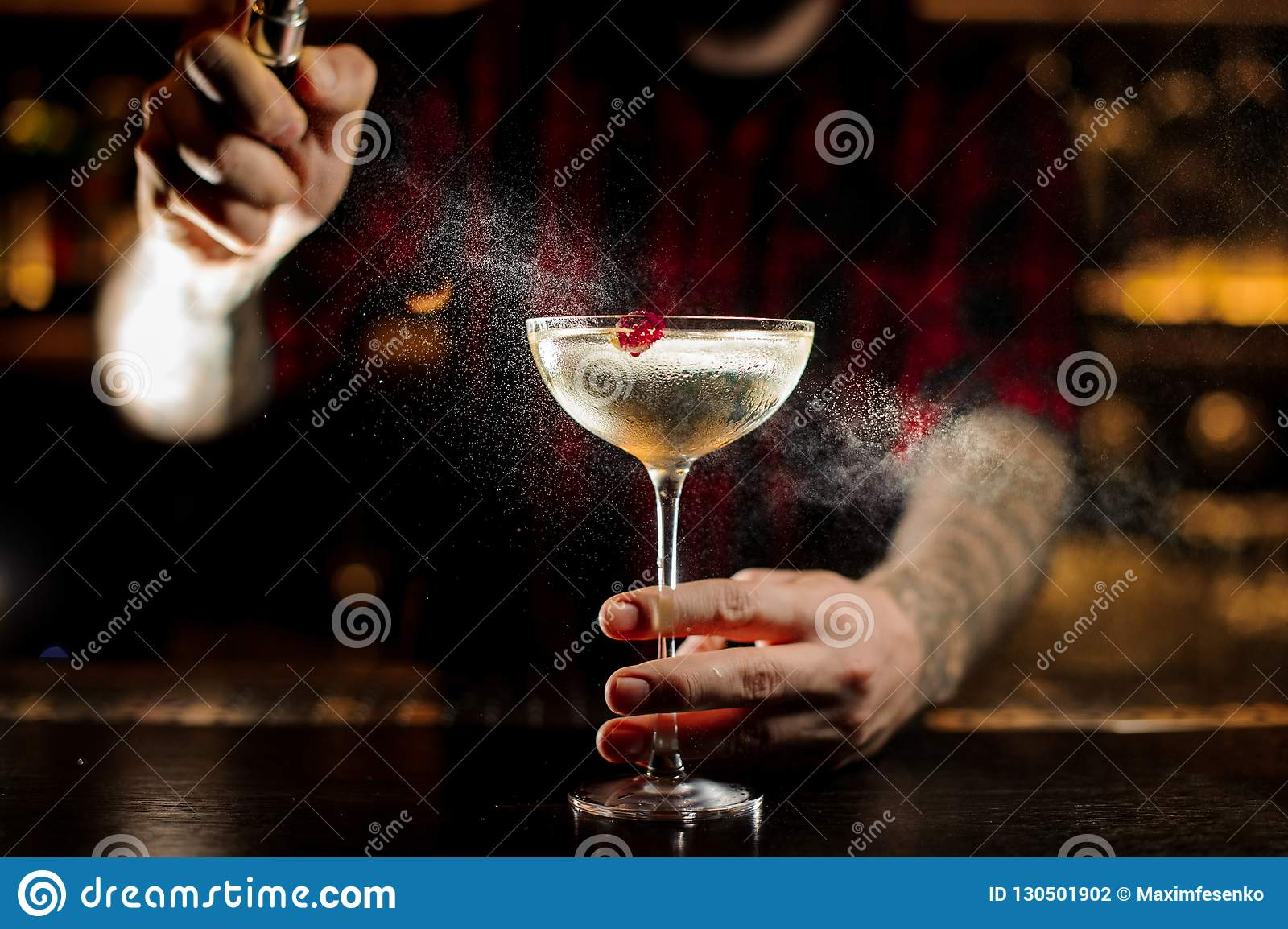 Bartender spraying on the Twinkle cocktail in the bar