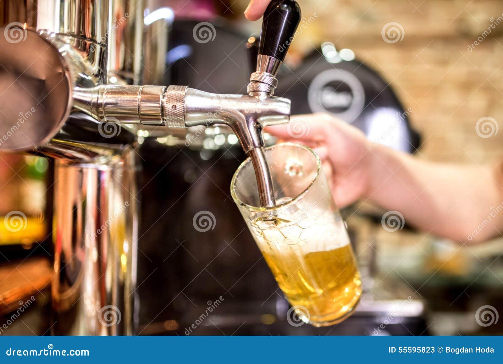 Bartenderhänder på öl knackar lätt på att hälla en portion för utkastlageröl i en restaurang eller en bar
