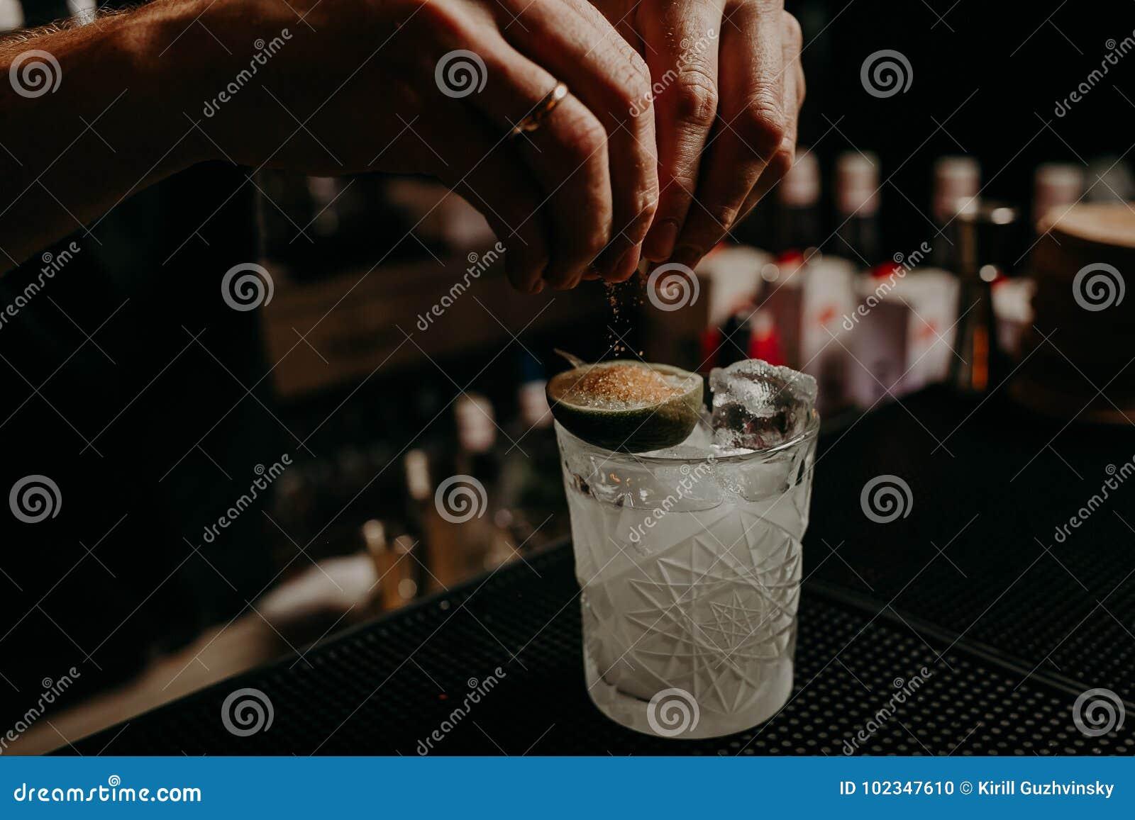 Bartendern dekorerar coctailen med citronen ingen framsida