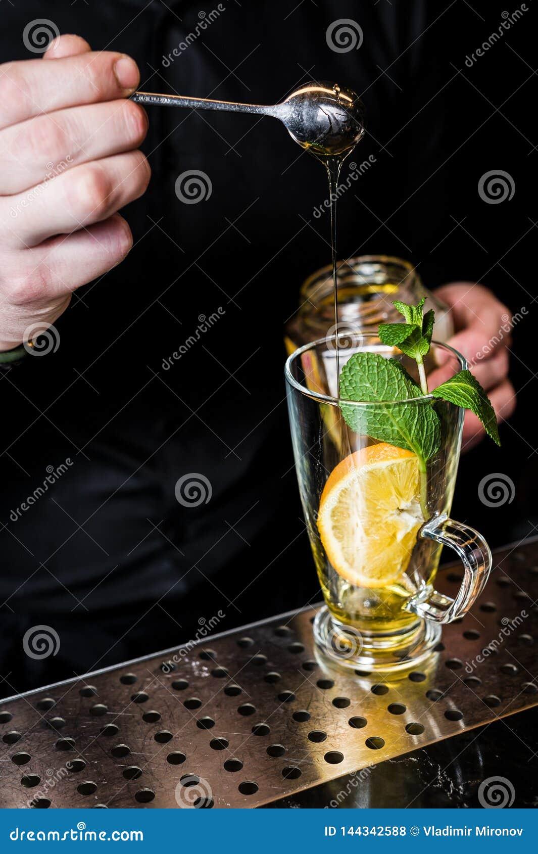 Bartendern förbereder fruktte med tranbär i ett exponeringsglas, mörk bakgrund