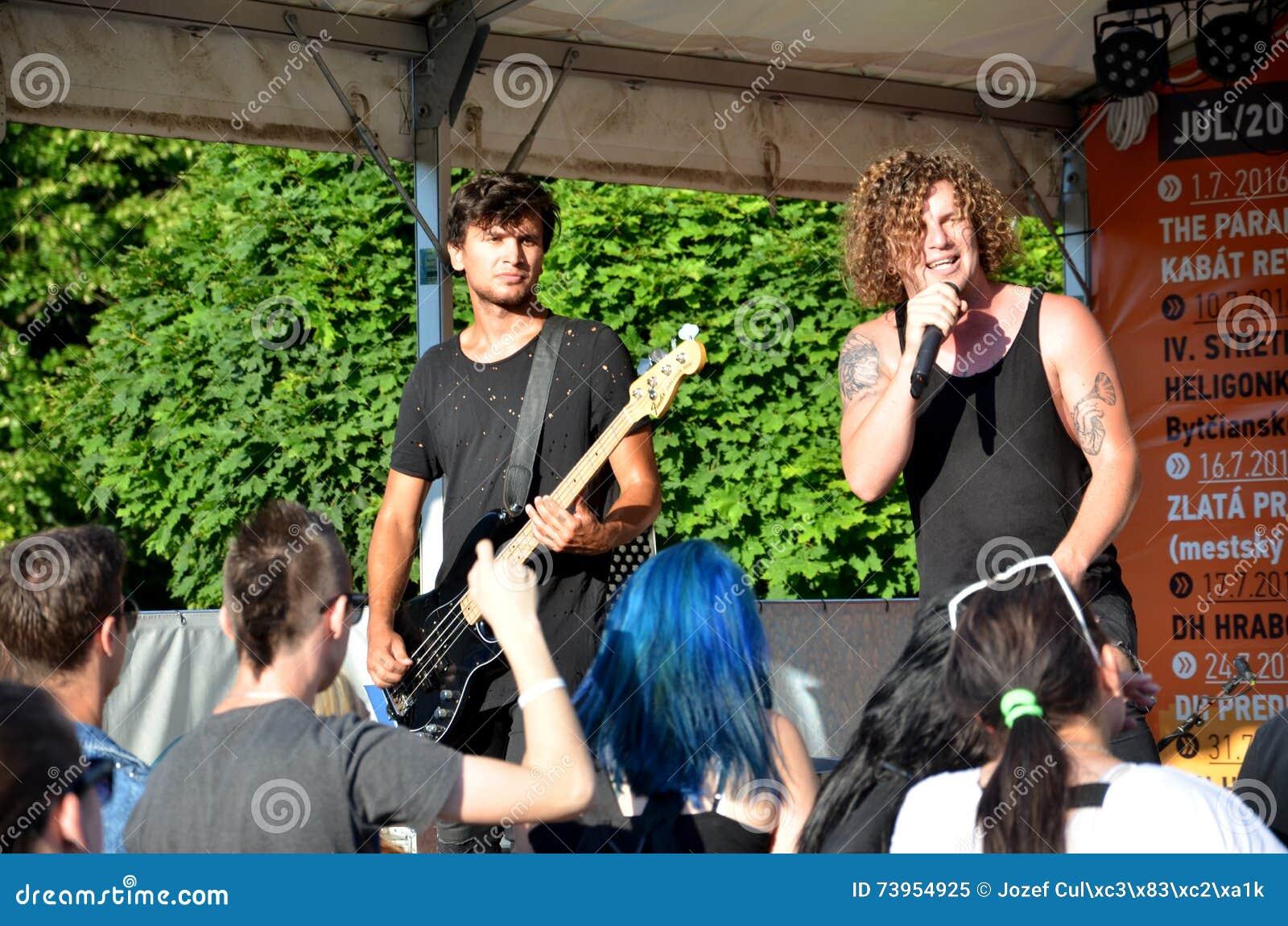 Bas- gitarrist och tatuerad sångareställning framme av gruppen av tonåringar