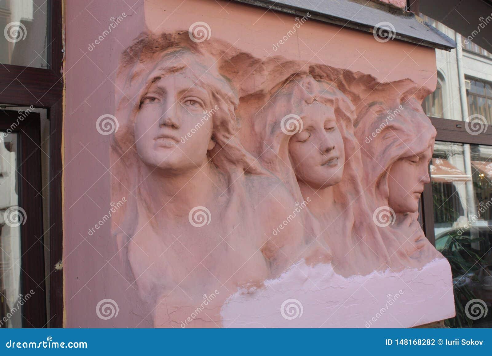 Bas-hulp van de hoofden van vrouwen op de voorgevel van het gebouw in Petersburg