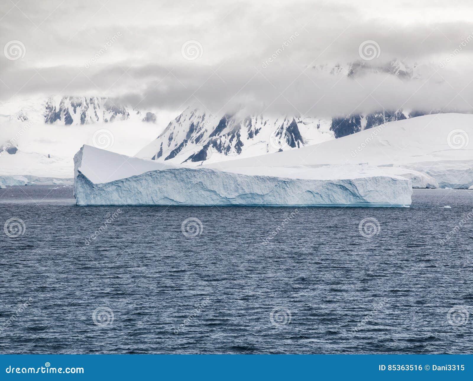 Bas nuages et icebergs entourant le littoral montagneux