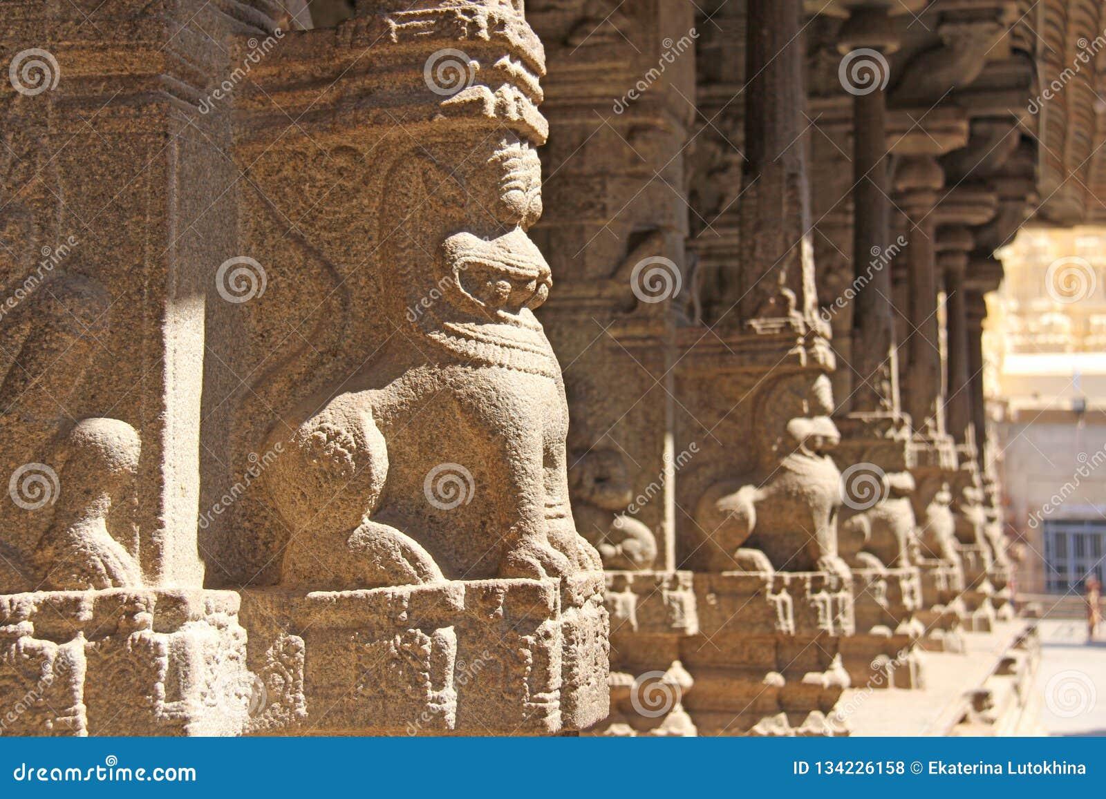 Bas-relevos de pedra na coluna em Shiva Virupaksha Temple, Hampi Cinzelando o fundo antigo de pedra Figuras cinzeladas feitas da