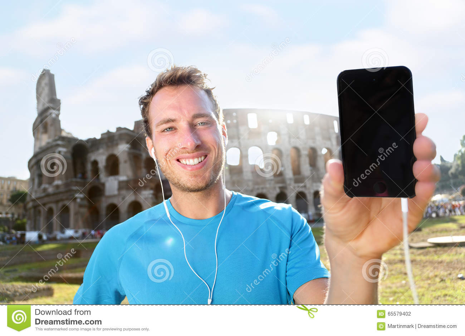 Basculador de sorriso que mostra Smartphone contra Colosseum