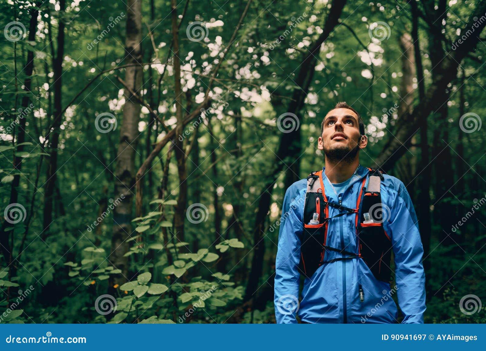 Basculador masculino apto que descansa durante el entrenamiento del día para la raza del rastro del bosque del campo a través en