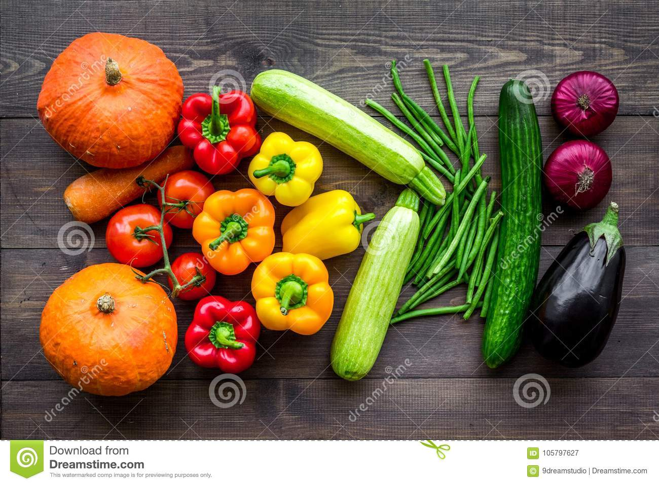Base of healthy diet. Vegetables pumpkin, paprika, tomatoes, carrot, zucchini, eggplant on dark wooden background top