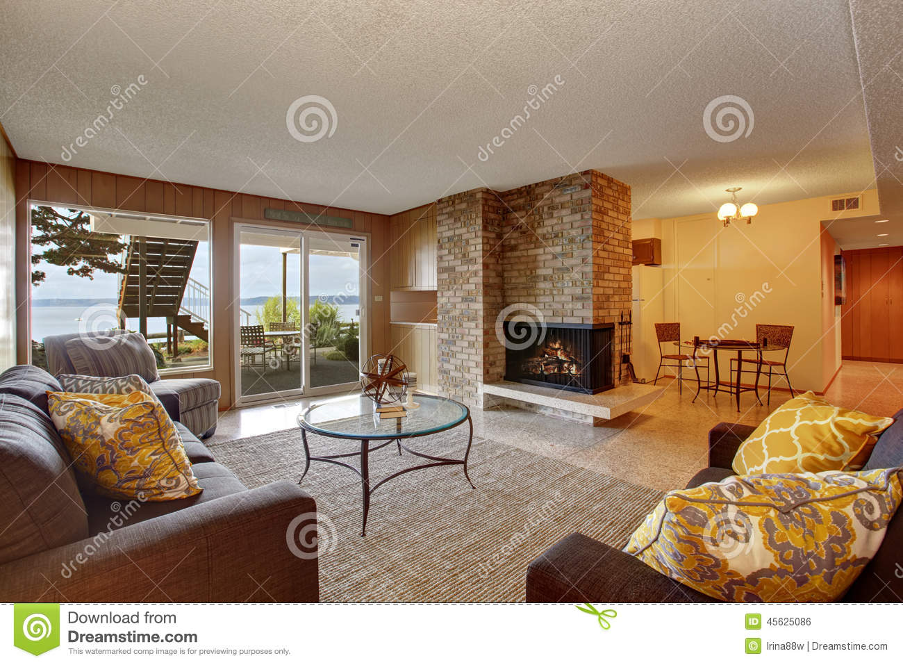 seminterrato interior design : Basement living room with wooden wall trim, brick fireplace and exit ...