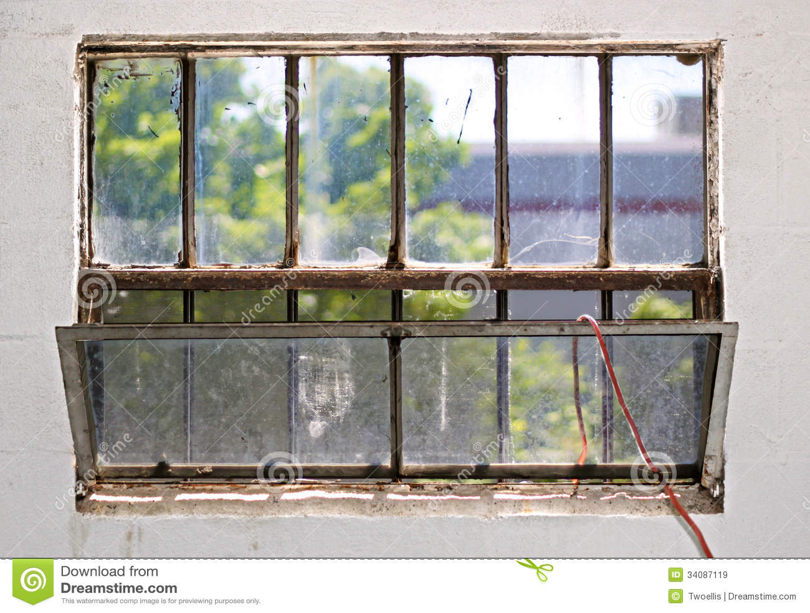 grungy dirty rust basement casement window with an old red garden