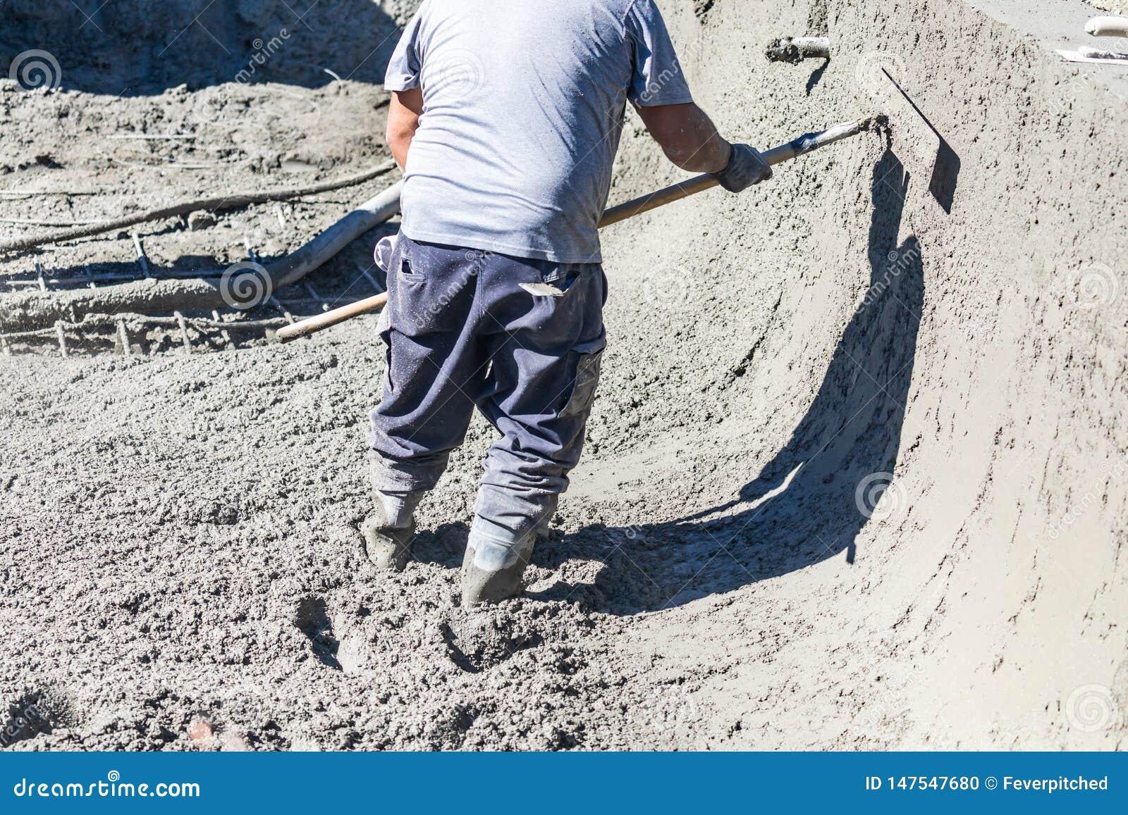 Basenu pracownik budowlany Pracuje Z Bullfloat Na Mokrym betonie