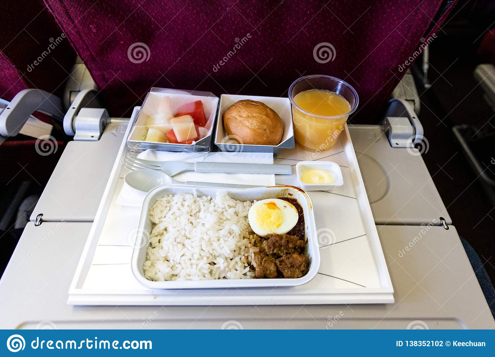 Basic inflight meal consisting rice, egg, beef curry, bread, juice