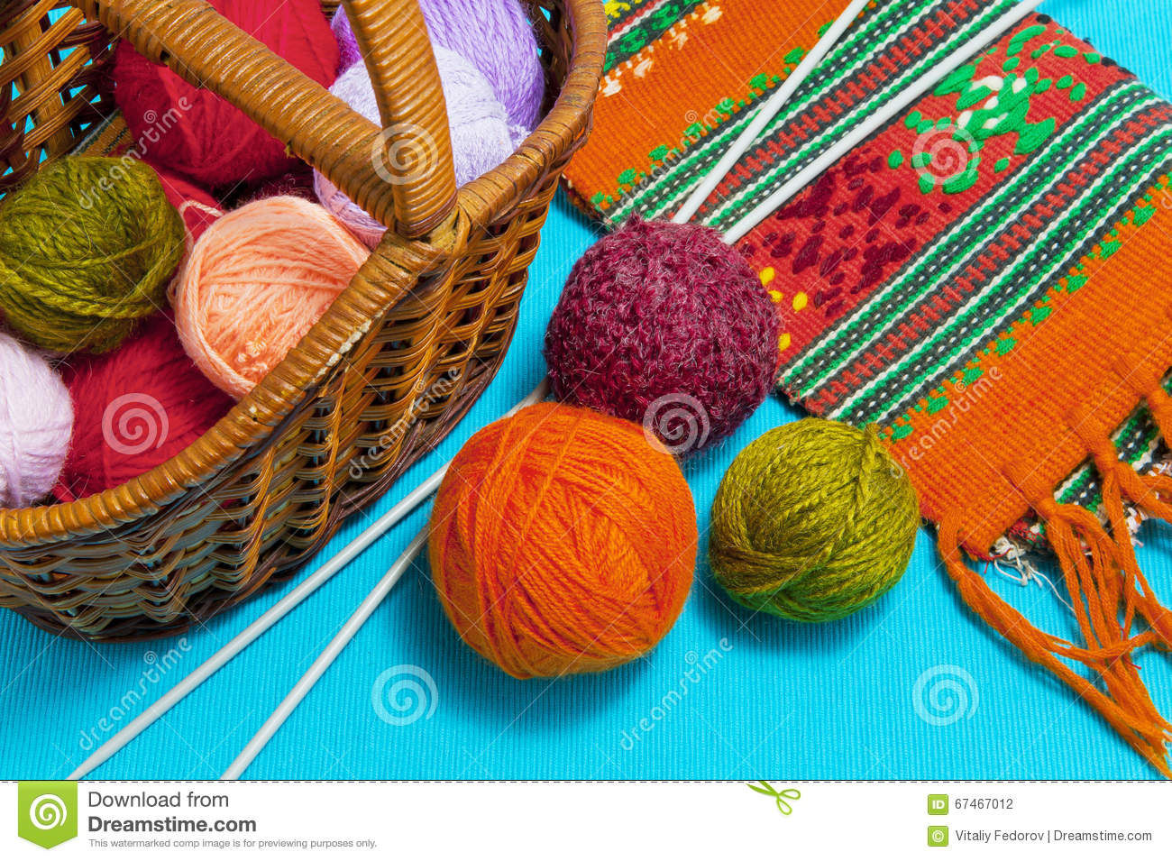 Basket with balls of wool and knitting needles on a blue background