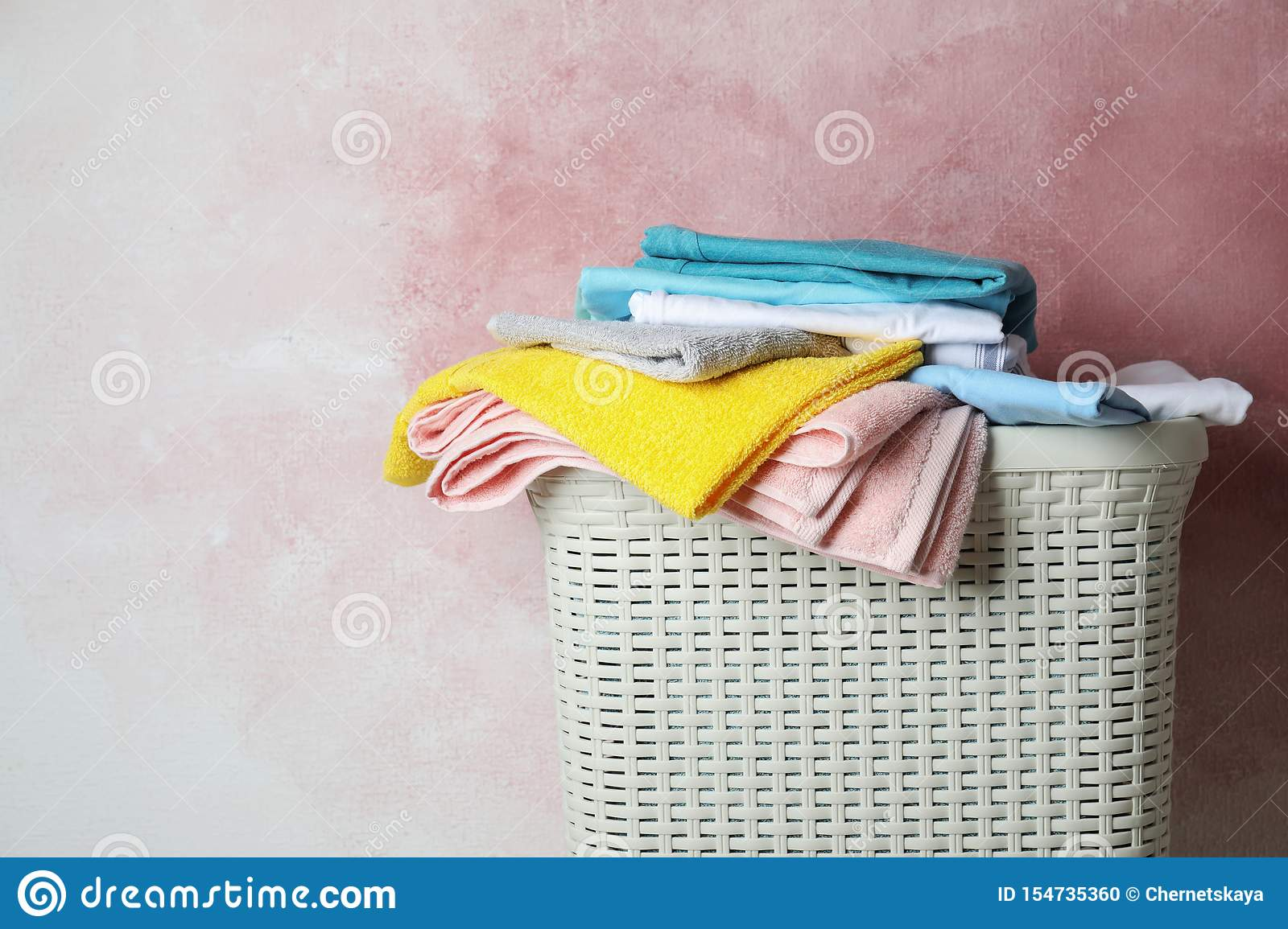 Basket with clean laundry on pink background, space for