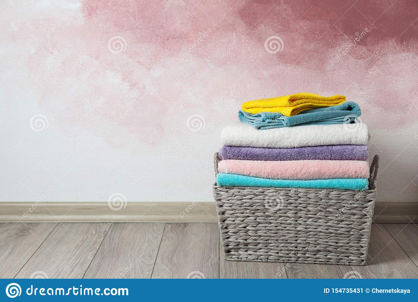 Basket with clean laundry on wooden floor near pink wall, space for