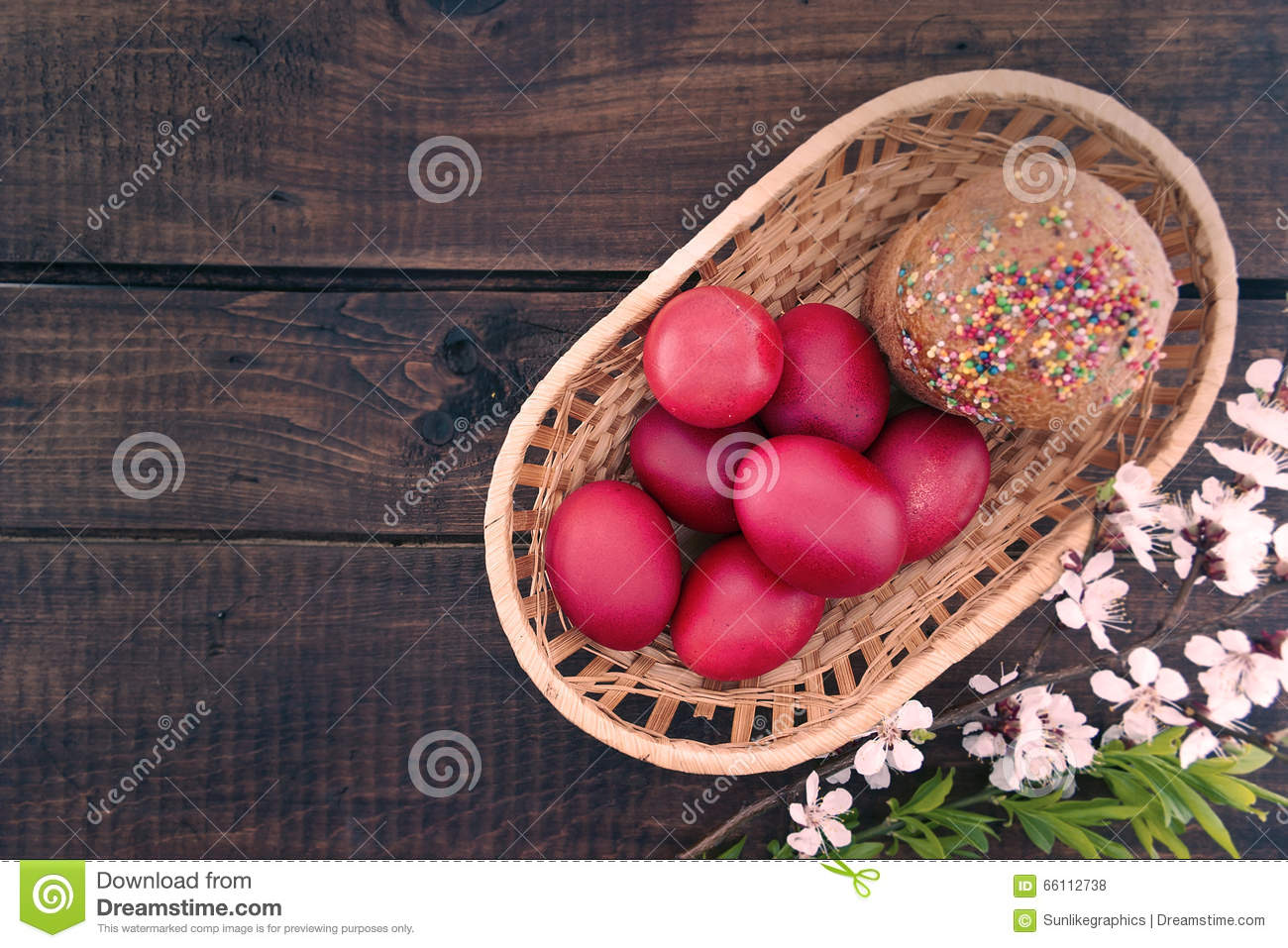 Basket with easter cake and red eggs on rustic wooden table. Top