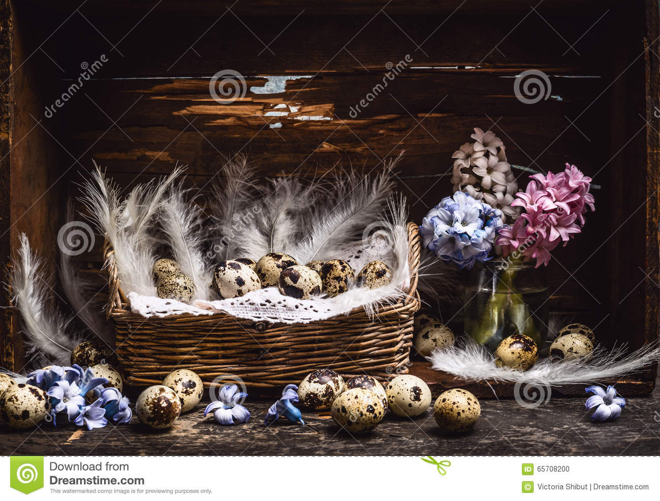 Basket with quail eggs and feathers and spring flowers Hyacinths bunch on vintage wooden table, over rustic background, side view