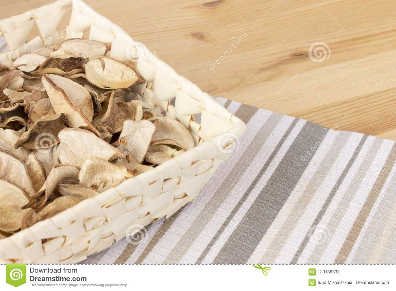 Basket with spicy dry plants on a light wooden background, covered with striped cloth