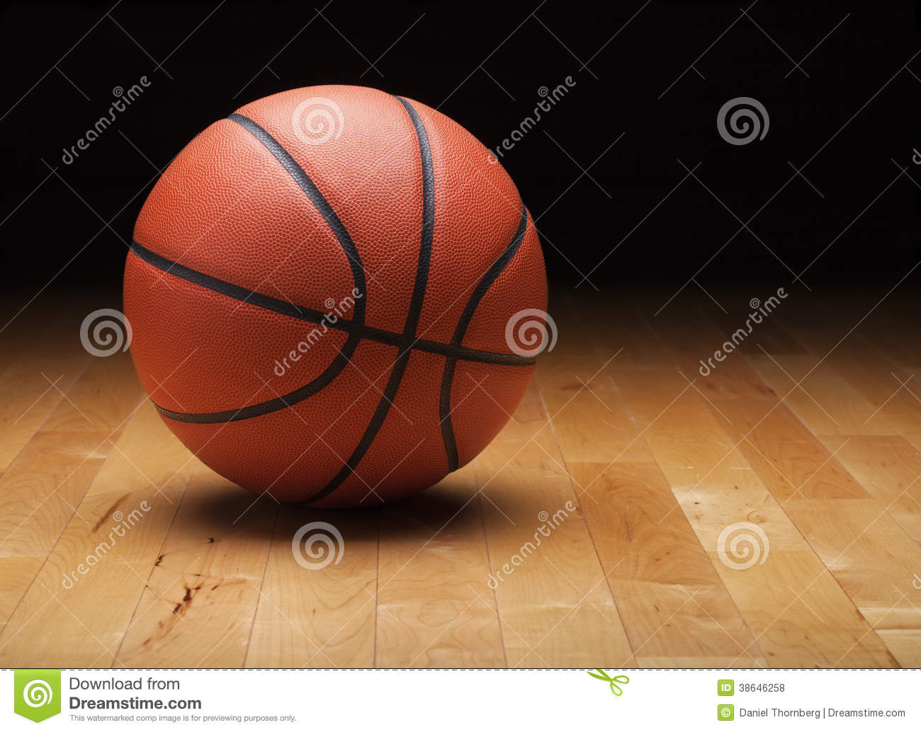 basketball with dark background on wood gym floor stock