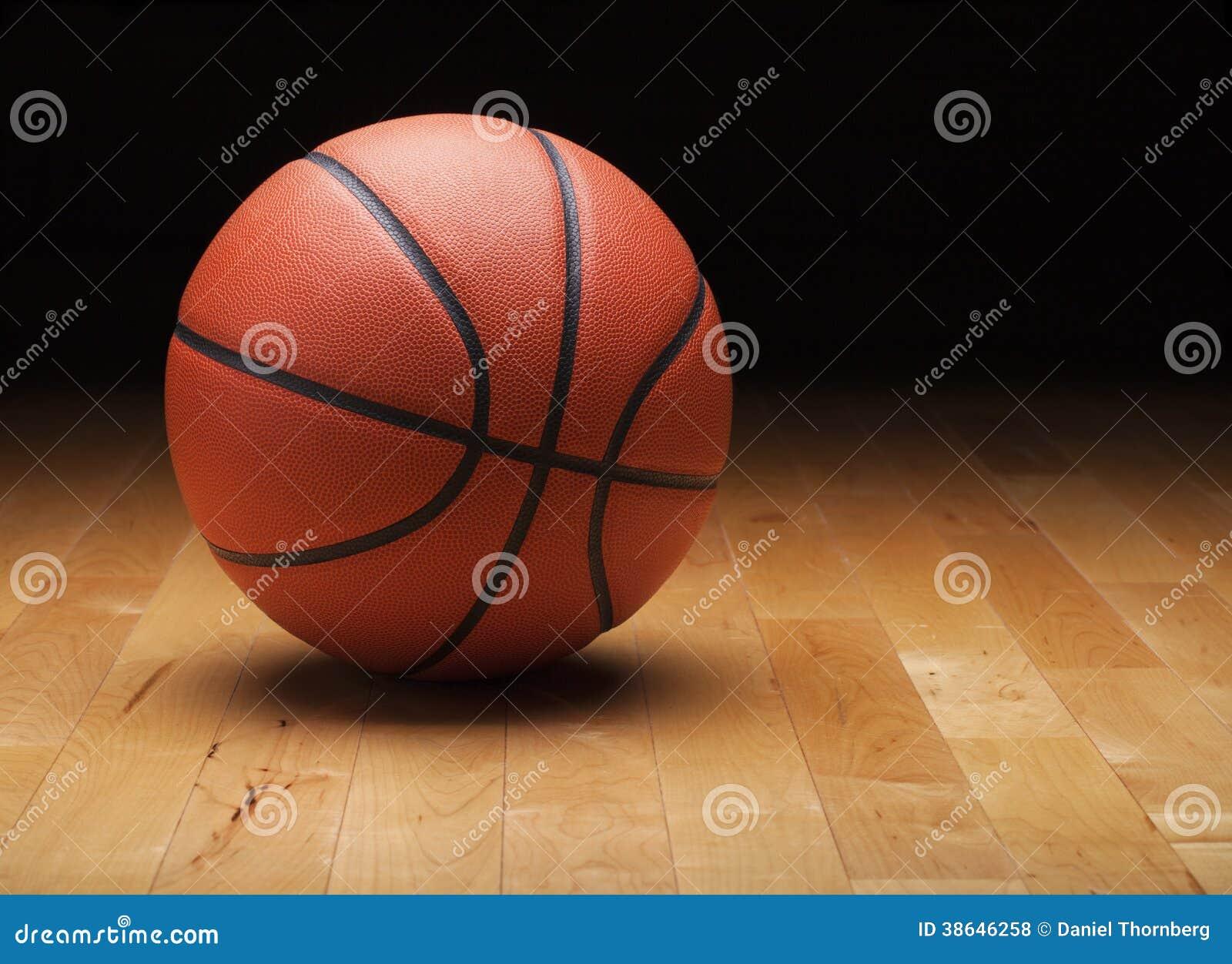 Basketball mit dunklem Hintergrund auf hölzernem Turnhallenboden