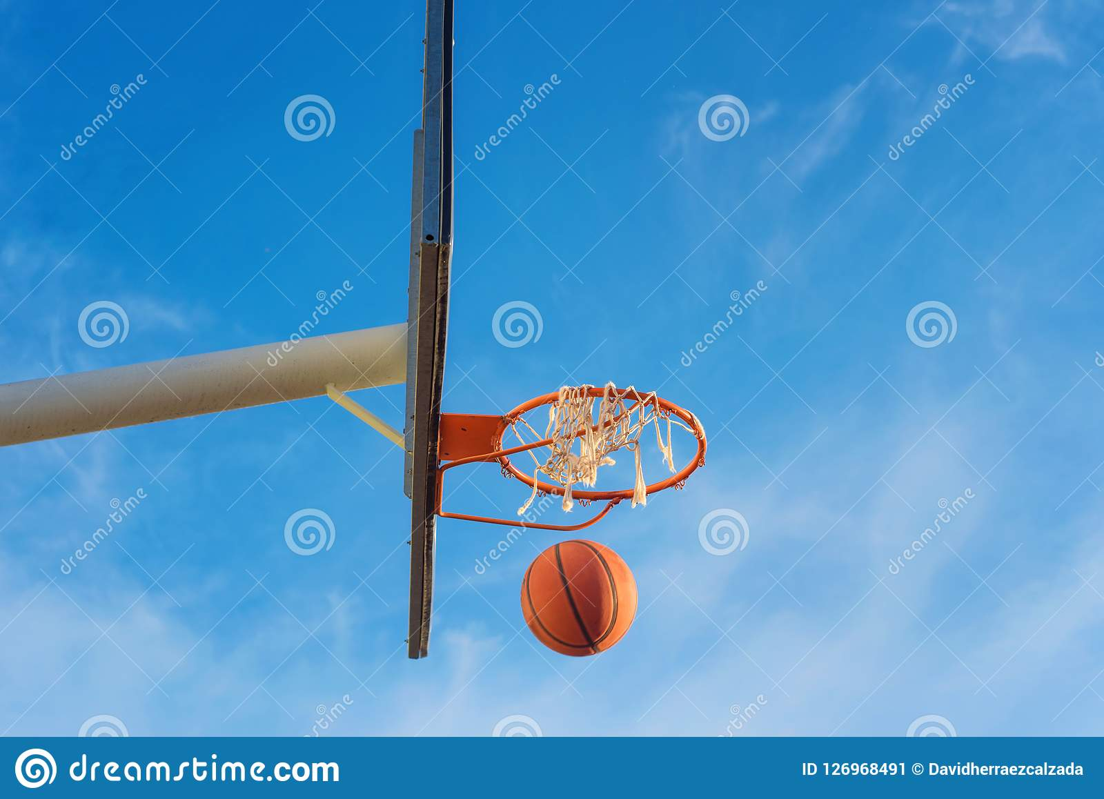 Basketball shield, ball flying to basket on blue sky background