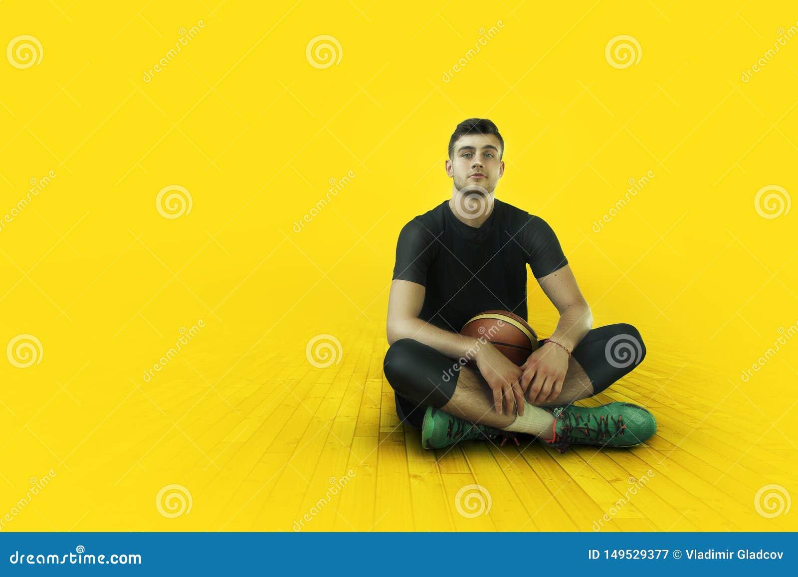 Basketballer joven del deportista en la luz roja del contraste