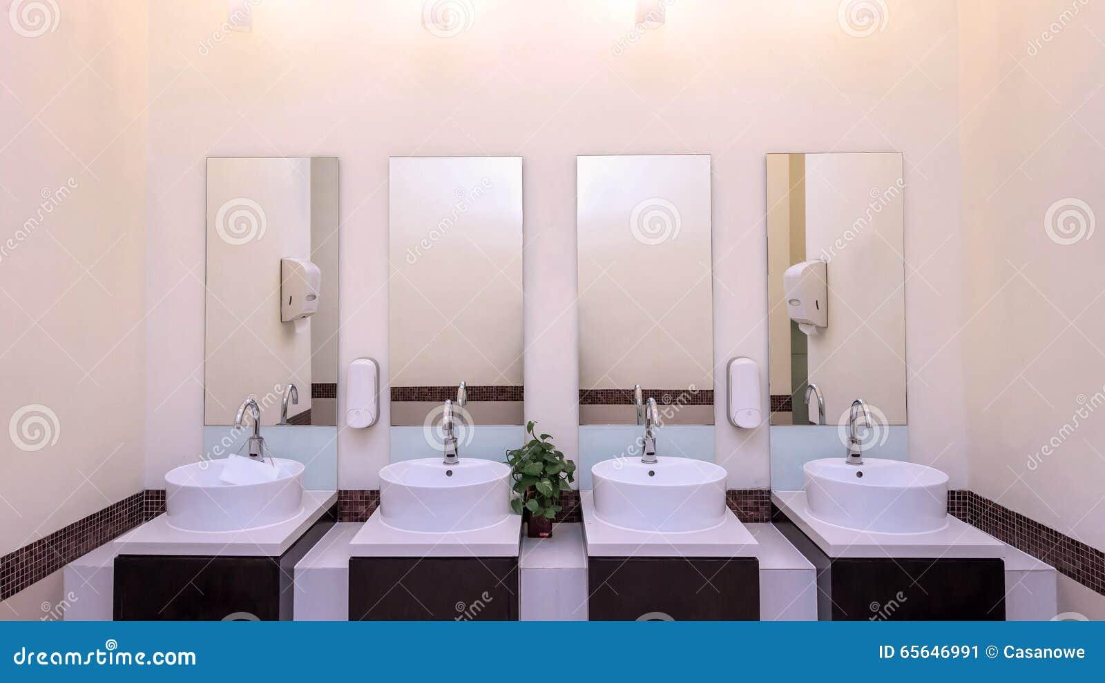 Bassins blancs dans l intérieur de salle de bains avec les tuiles granitiques