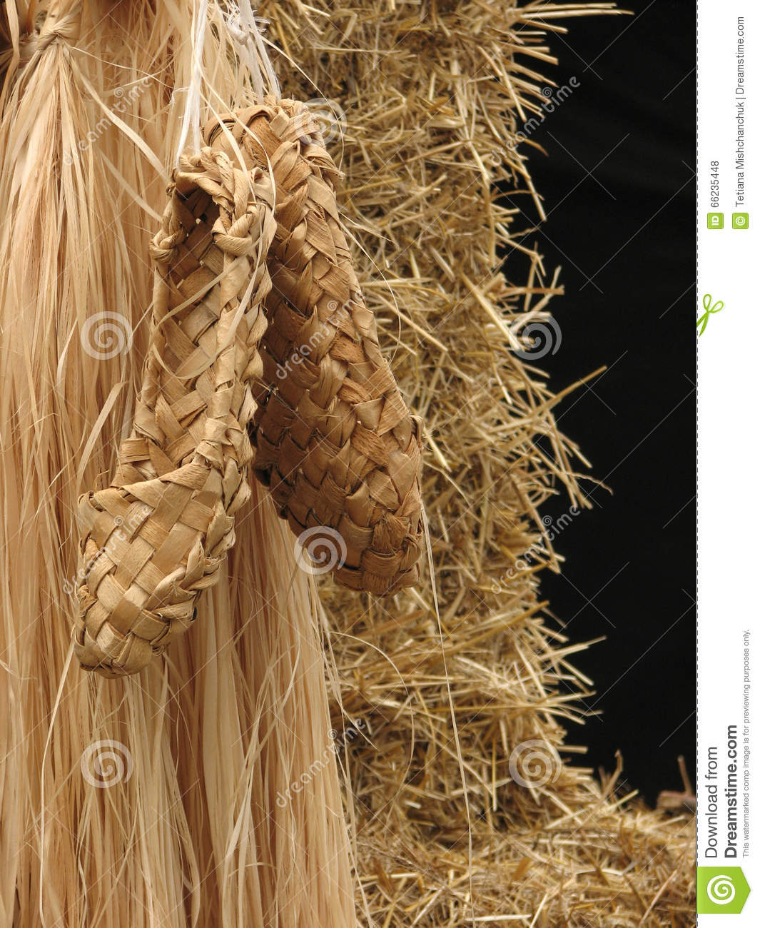 Bast shoes on background of bast and straw