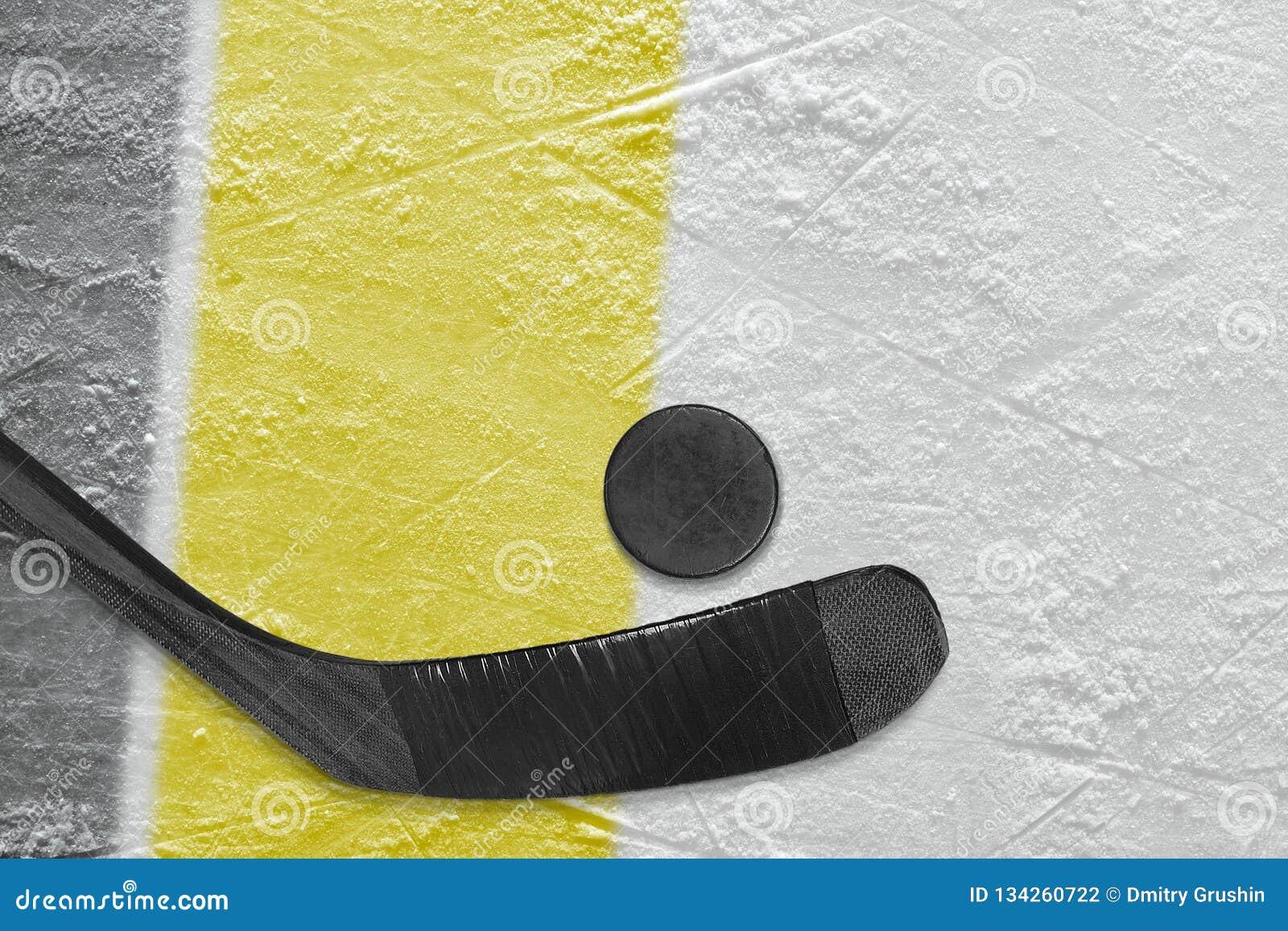 Bastone, disco e frammento di hockey dell arena del ghiaccio con le linee nere e gialle