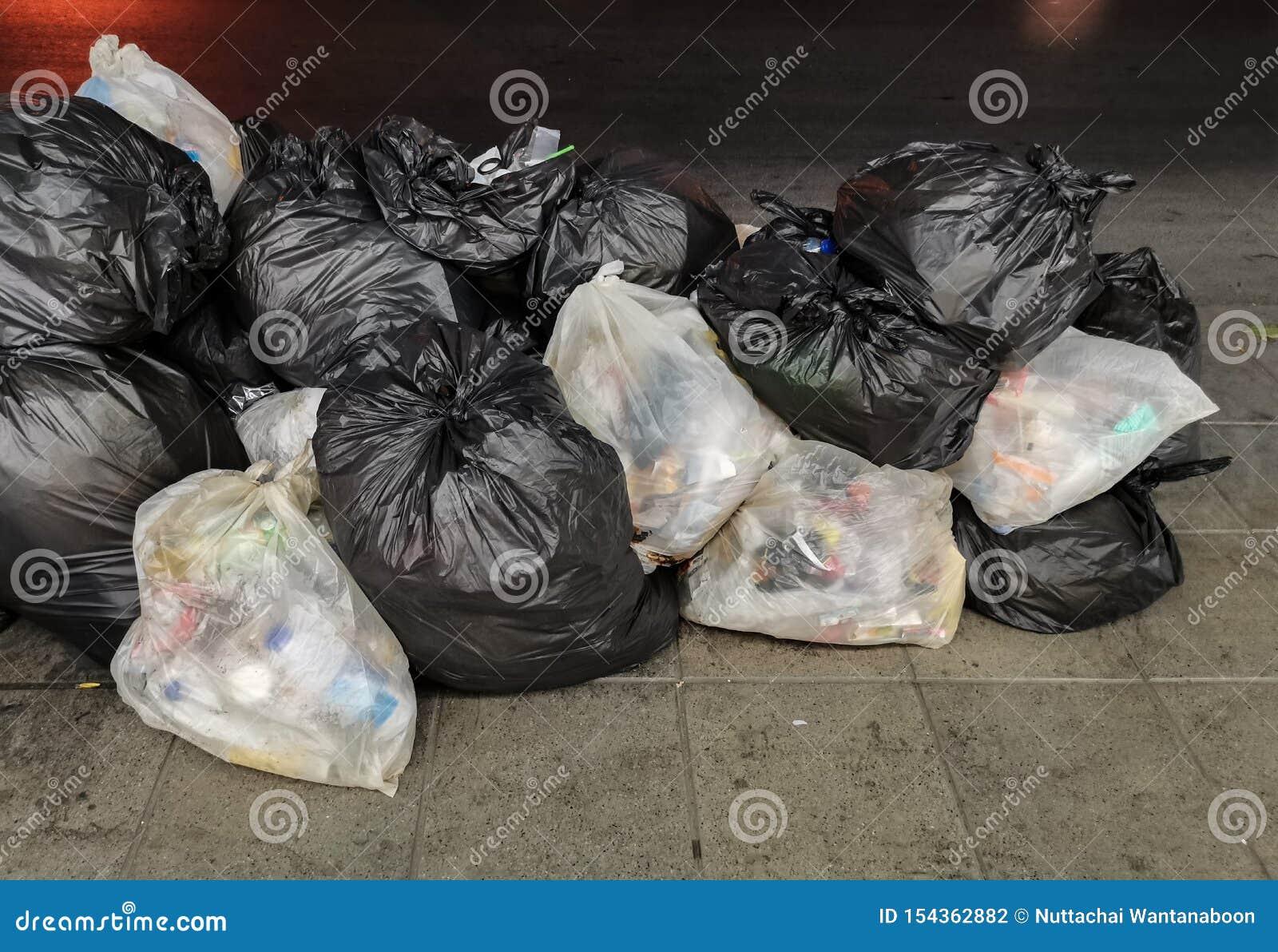Basura - el montón de basura en el bolso blanco y negro se junta en el sendero, borde de la carretera en la ciudad, espera para l