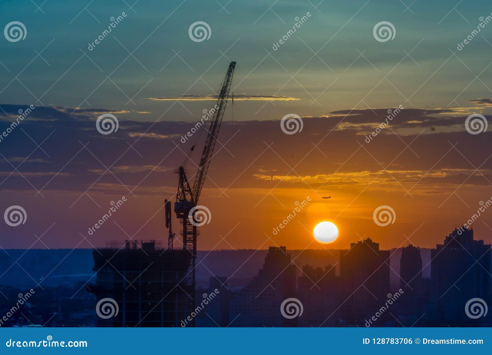 Basztowy żuraw na budowie przy wschodem słońca