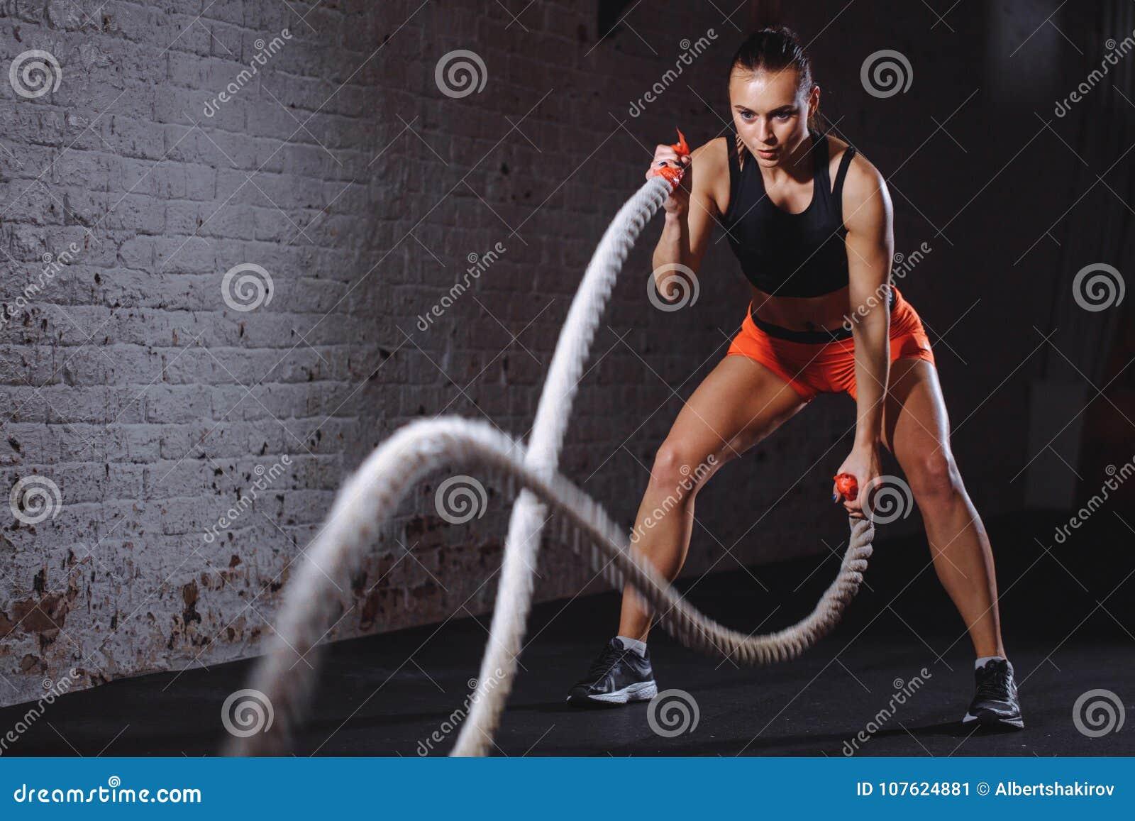 A batalha ropes a sessão Os jovens atrativos couberam e tonificaram o treinamento do desportista no gym