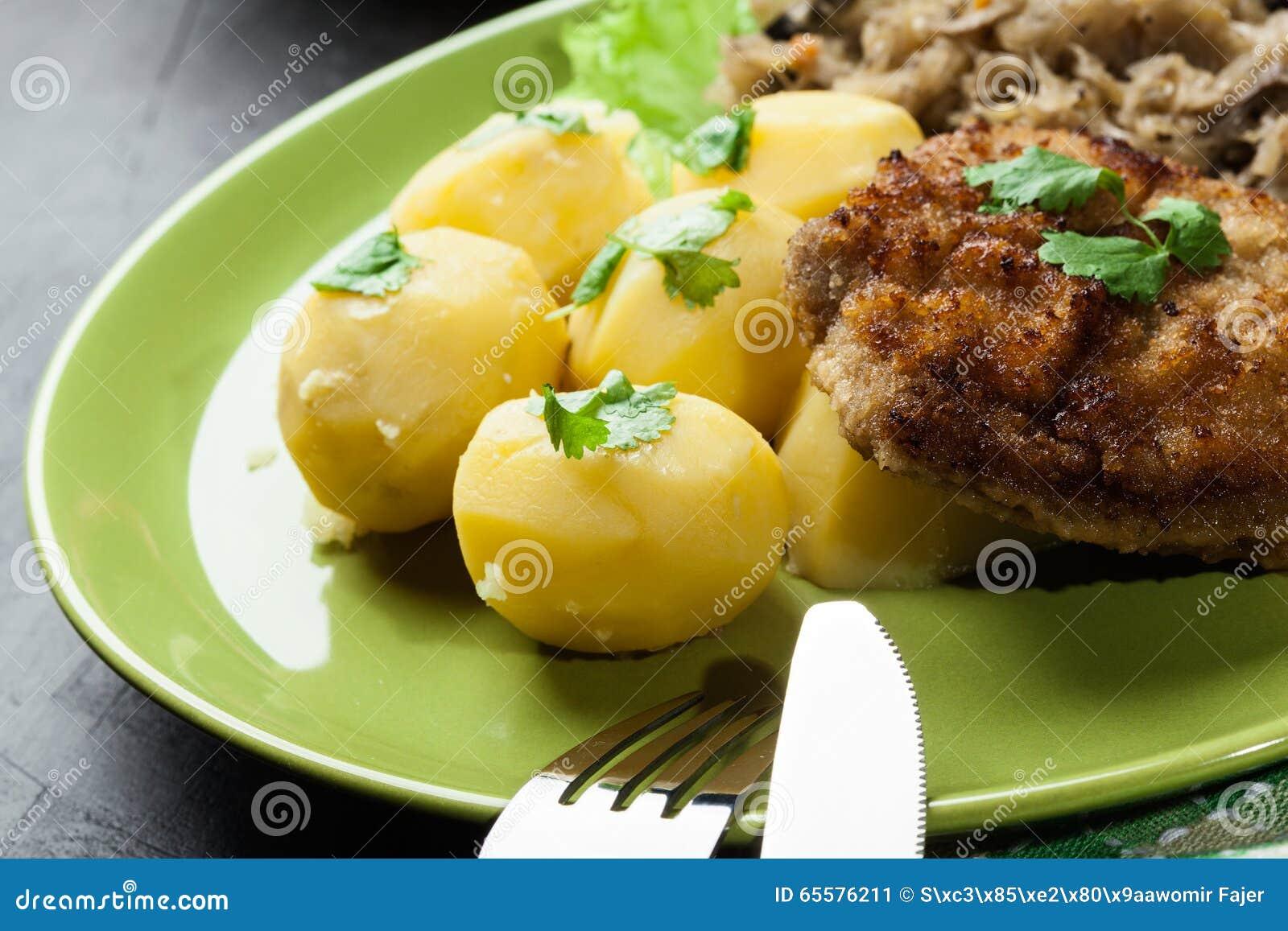 Batatas fervidas com a costeleta de carneiro fritada da carne de porco e o chucrute fritado