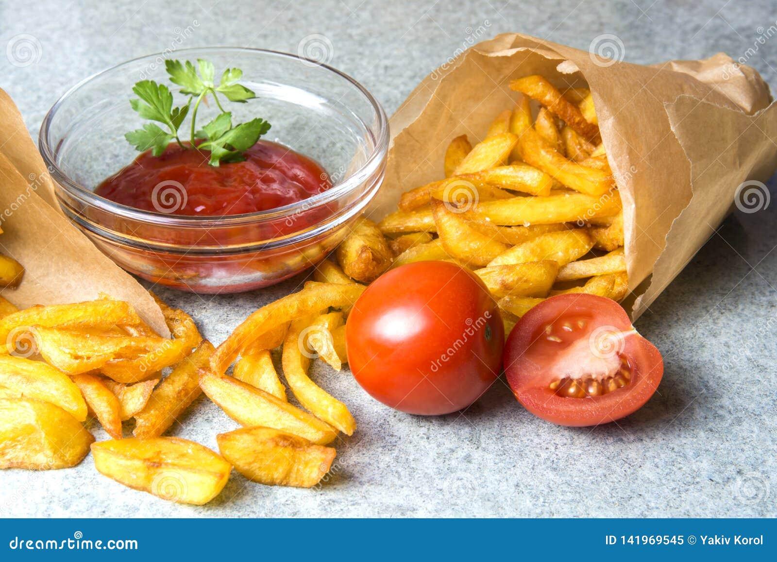 Batatas fritas, batatas fritadas com ketchup e tomates no fundo do granito cinzento-azul